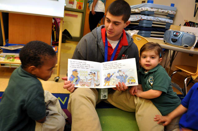 Fairfield's Sacred Heart University student Tom Barcia works with students in the Lighthouse Program at the Discovery Cultural Magnet School in Bridgeport.