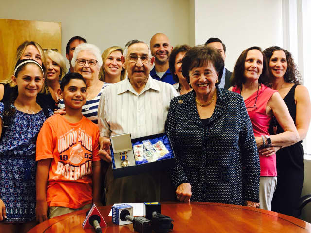 Alfred Magnatta receives his medals from Congresswoman Nita Lowey.